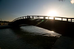 Bridge over a small river. People crossing a small bridge over a river in the morning light stock photo