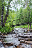 A bridge over a small stream with large rocks in the green forest. royalty free stock image