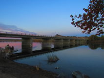 Bridge over river at sunset Stock Images