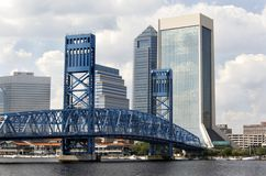 Bridge over the St. Johns River. Blue bridge over the St. Johns River with glass office buildings and retail stores in the background. Underneath the bridge are Royalty Free Stock Images
