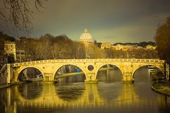 Bridge over the Tevere. Rome, Italy. Bridge over the Tevere river. Rome, Italy. Toned image. Saint Peter`s basilica in the background Royalty Free Stock Photography