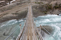 Bridge over troubled glacial water Royalty Free Stock Images