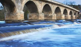 Bridge Over Troubled Water. Hexham Bridge in Northumberland, England with water flow long exposure stock photo