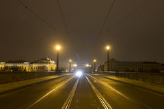 A bridge over Vltava river at night with a car approaching form the far end royalty free stock photography
