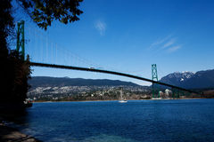 Bridge Over Water. Lion's Gate Bridge, Vancouver on a clear day with a sailboat going under Royalty Free Stock Photos