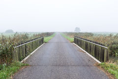 Bridge over water in a misty morning rural landscape in the Neth Stock Photography