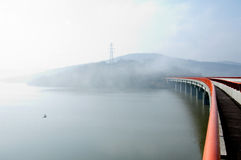 Bridge over the waved lake in the foggy morning Royalty Free Stock Image