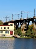 The bridge that stands in the water. The bridge over which freight trains move. Nearby is the river and the building. stock images