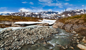 Bridge over a wild mountain river, snowy mountains in background. Bridge over a wild mountain river, that has two shoulders and is partially covered by melting Stock Photography