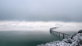 Bridge over wintry lake. Aerial view of curved bridge over wintry lake Royalty Free Stock Image