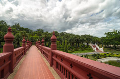 Bridge painted in red leading to a green park with palm trees. And other tropical greenery Royalty Free Stock Image