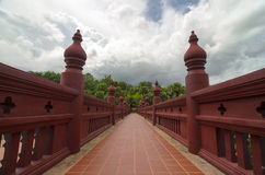 Bridge painted in red leading to a green park with palm trees. On a summer day Royalty Free Stock Image