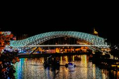 The Bridge of Peace is a bow-shaped pedestrian bridge, a steel and glass construction illuminated with LEDs, in Tbilisi. The Bridge of Peace is a bow-shaped stock images