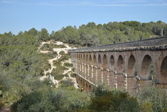 Bridge. Stone bridge. Antique. Spain.. Pedestrain to the other side, two banks of bridge with forest, spring and green trees. Track Royalty Free Stock Images