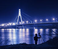 Bridge photo. Silhouette of photographer with camera & tripod in front of bridge at night Royalty Free Stock Photo