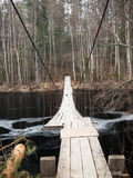 Bridge of planks and wires hanging over the river Stock Photos