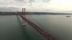 Bridge Ponte 25 de Abril over the Tagus river in Lisbon, Portugal at evening aerial view. Transportation on 25 April bridge in Lisbon stock footage