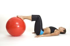 Bridge Pose 3. A female fitness instructor demonstrates the starting position of the yoga bridge pose using a fitball Stock Image