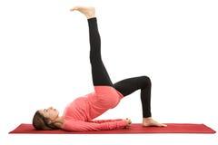 Bridge pose with a leg raise. Caucasian woman doing bridge pose with a leg raise. Isolated on white background Stock Images