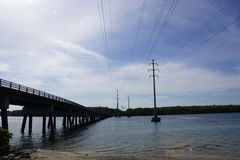 Bridge and Power lines cross waterway Royalty Free Stock Photo