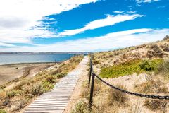 Bridge in Puerto Madryn beach, sun, waves and sand, beautiful day. Puerto Madryn beach, sun, waves and sand, beautiful day stock photo