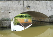 Bridge in Putim. Old stone bridge in village Putim known from book of Jaroslav Hasek `Good Soldier Svejk` with mirroring house in water of river Blanice under Royalty Free Stock Images