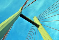 The bridge pylons on the ropes against the blue sky in the clouds. Architectural details of modern building Royalty Free Stock Photo