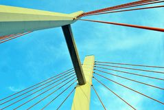 The bridge pylons on the ropes against the blue sky in the clouds. Architectural details of modern building Stock Photos