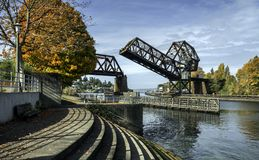 Bridge Raises over Waterway during Autumn in Seattle. The Salmon Bay Bridge over the Ballard Locks in Seattle Raises on a Sunny Autumn Afternoon Stock Photography