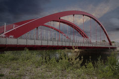 Bridge. Red bridge over a river with stormy sunset clouds Stock Photo