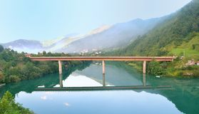 Bridge reflecting in a green river, green hills and mountains in the bacground Stock Image