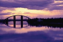 Bridge reflection in water surface of river Dnieper duaring sunset time. Toned image: purple, violet, yellow, orange colors Royalty Free Stock Photo