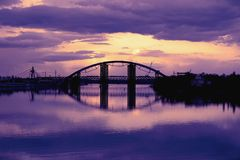 Bridge reflection in water surface of river Dnieper duaring sunset time. Toned image: purple, violet, yellow, orange colors Royalty Free Stock Image