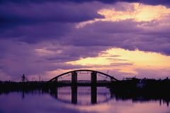 Bridge reflection in water surface of river Dnieper duaring sunset time. Toned image: purple, violet, yellow, orange colors Royalty Free Stock Photography