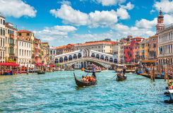 Bridge Rialto on Grand canal famous landmark panoramic view Venice. Italy with blue sky white cloud and gondola boat water Stock Photo