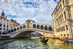 Bridge Rialto on Grand canal famous landmark panoramic view Venice Italy with blue sky white cloud and gondola boat water. Stock Photos