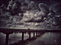 Bridge on the river with clouds in monotone style. Black and white background royalty free stock photos