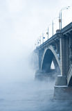 Bridge on river in cold steam. On blue Stock Photos