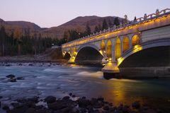 Bridge and river at dusk. Slow shutter for river at dusk and a bridge just has lights on stock photos