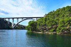Bridge on the river.Green coast with pine trees stock image