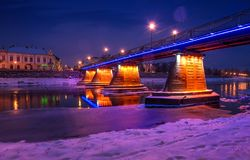Bridge through the river Uzh at night. Beautiful cityscape of old european town Uzhgorod in winter Stock Images