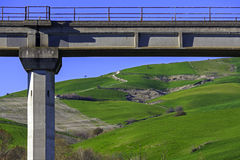 A bridge road in green hills with serpentine road Royalty Free Stock Images