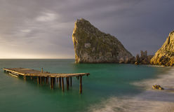Bridge and rock. Rock and bridge standing in the sea Stock Images