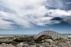 Bridge on the rockland near the sea Stock Photography