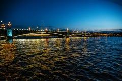 Bridge in Saint-Petersburg with lights illumination in summer white night, Neva river. Toned Stock Photo