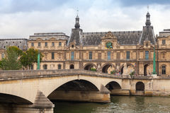 Bridge on Seine river with Louvre museum facade Stock Photos