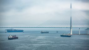 Bridge and ships in the fog in cloudy weather stock images