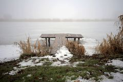 Bridge on the shore of a winter lake stock photos