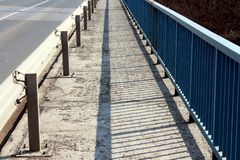 Bridge sidewalk with guardrail and fence. Bridge sidewalk with sand on cracked asphalt between guardrail on left and metal fence on right side on warm sunny day Stock Image