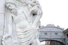 Bridge of Sighs, in Baroque style, Venice, Italy. In the foreground one of the sculptures (Noah drunk) of the Ducal Palace in the background, out of focus, the Stock Image
